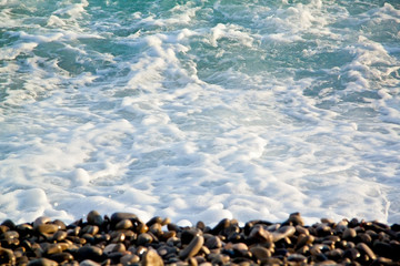Azure sea waves. Clear blue water with white foam. Pebbles on th