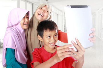 three muslim kids playing tablet computer