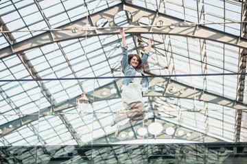 happy woman jumping up high at airport