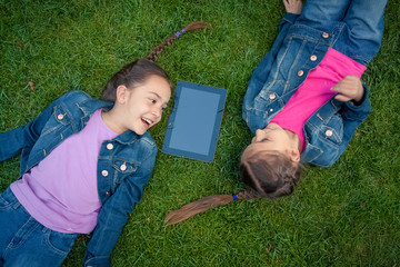 little girls lying face to face on grass and looking at tablet