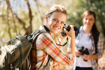 young woman taking photos of her friend