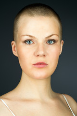 Portrait of young woman with shaved hairstyle against dark backg