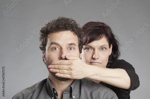 Frau hält Mann den Mund zu. Stockfotos und lizenzfreie