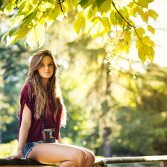 Portrait of young woman with vintage camera outdoors in a park.