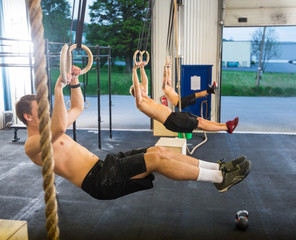 Athletes Dangling On Gymnastic Rings in Box