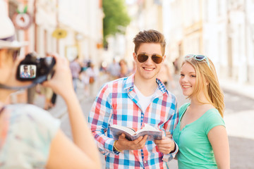 smiling couple with map and photo camera in city
