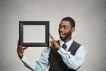 Happy businessman holding empty picture frame open to new ideas