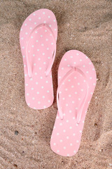 Color flip-flops on sand background