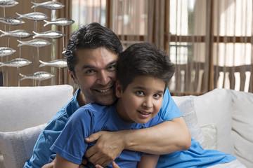 Adult man hugging his son while sitting at sofa