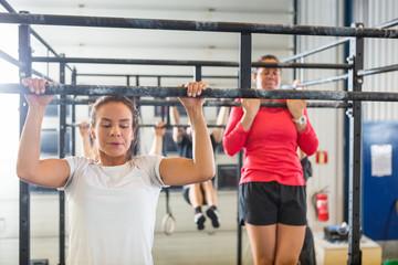 Athletes Doing Chin-Ups At Gym
