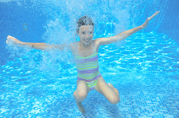 Active underwater child swims in pool, girl swimming