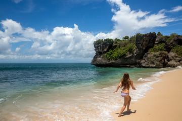 Young woman running along shore of ocean