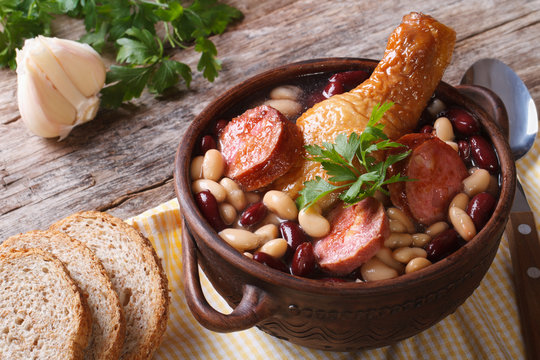 Bean soup with chicken legs and sausages in a bowl