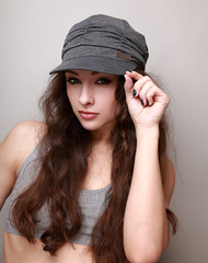 Sexy hip hop girl in trendy cap looking holding the cap