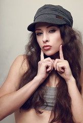 Hip-hop girl in hat posing and showing kissing sign