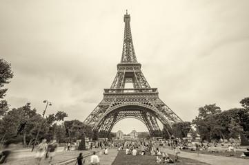 Tourists enjoying Eiffel Tower view from Champs de Mars gardens