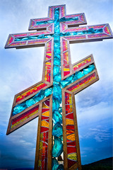 Stained glass orthodox cross on blue sunset sky closeup