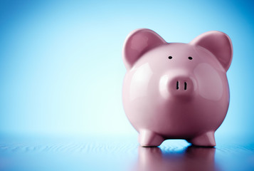 Pink piggy bank on a colorful blue background
