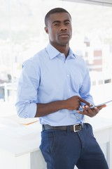 Serious businessman using tablet pc looking at camera