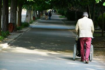 hombre empujando una silla de ruedas por un paseo urbano