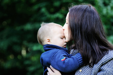 Young mother kissing her son