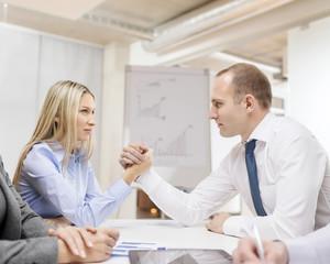 businesswoman and businessman arm wrestling