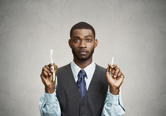 Man holds cigarette and toothbrush, bad smoker breath concept
