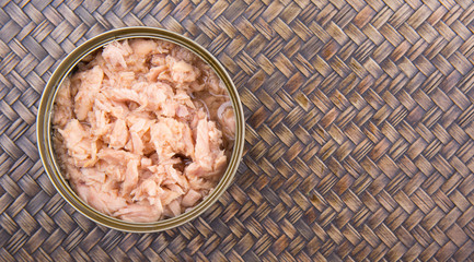 Pieces of tuna fish in a can over wicker background