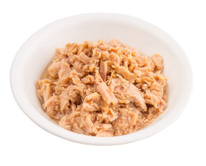 Flaked tuna pieces in a white bowl over white background