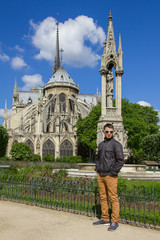 Young man hipster in a glasses near Cathedral of Notre Dame de P