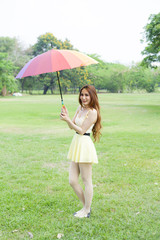 Woman with umbrella standing on the lawn.