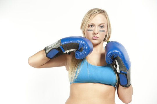 A young boxing model posing with gloves on a white background in a sportsbra.