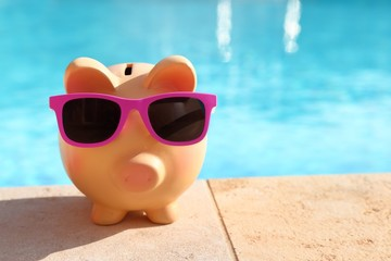 Summer piggy bank with sunglasses in front of a swimming pool Wall mural