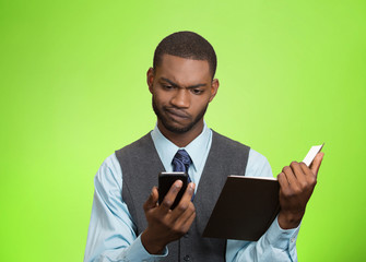 Skeptical man looking at phone holding book on green background