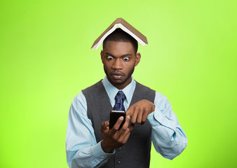 Shocked man holding mobile, book over head green background