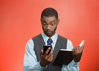 Shocked man looking at his smart phone holding book