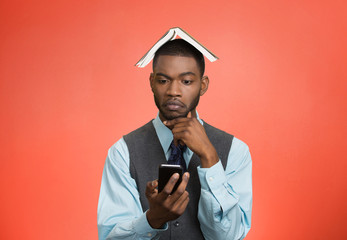 Man texting on mobile phone book over head confused