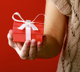 Female hand holding gift box isolated on red