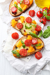Tasty bruschetta with tomatoes, on table