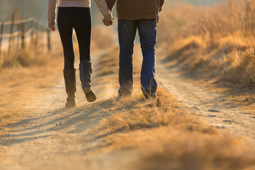 young couple holding hands walking on autumn path Wall mural