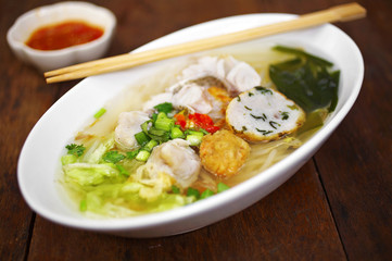 close up thai sweet soup noodle with fish in white cup