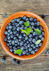 fresh blueberries in a bowl on wooden surface
