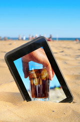 a tablet on the sand of a beach with a picture of a man with a g