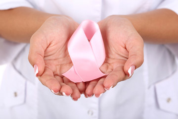 Woman with aids awareness pink ribbon in hands, close-up