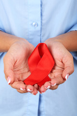 Woman with aids awareness red ribbon in hands, close-up