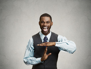 Angry man screaming to stop, time out gesture, grey background