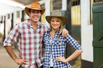 cowboy cowgirl couple inside stables