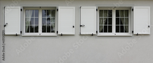 Moderne fenster fassade  Zwei moderne Fenster mit Klappläden in grauer Fassade