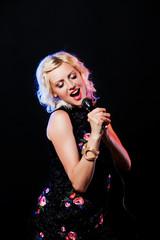 Beautiful singing woman with microphone. Singer. Karaoke song