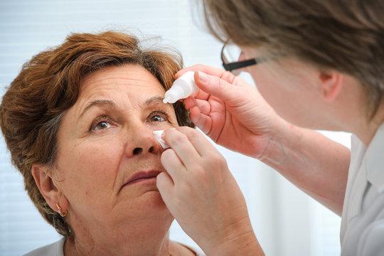 Senior woman applying eye drops